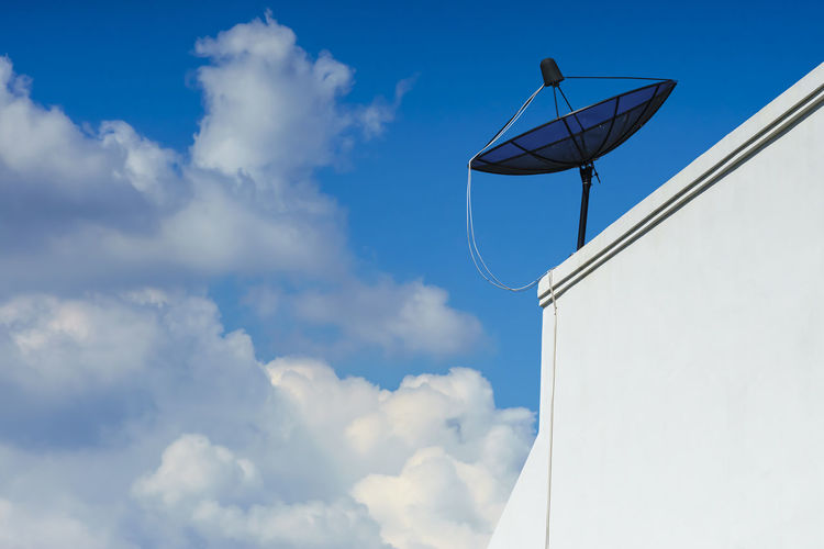 Low Angle View Of Satellite Dish On Retaining Wall Against Cloudy Sky