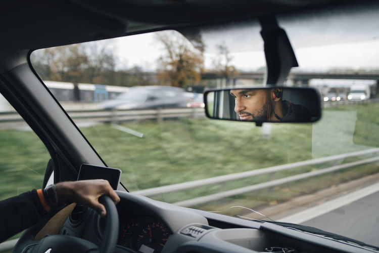 Portrait of man using mobile phone in car