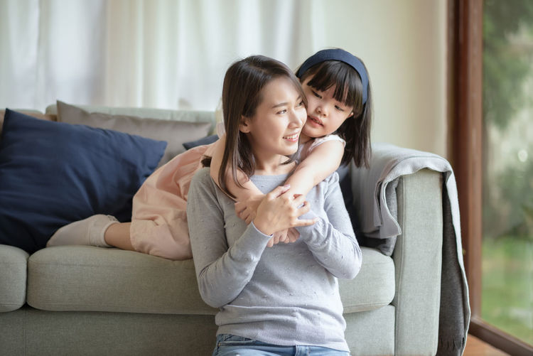 Happy mother and daughter sitting on floor