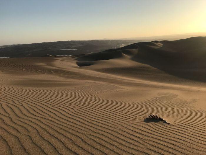 Scenic view of peruvian desert against sky during sunset.