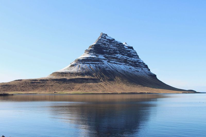 a photograph of the most photographed mountain in Iceland Kirkjufell Iceland Reflection Tourism Travel Nordic Mountain Nature Iceland Adventure Reykjavik Water Mountain Blue Lake Clear Sky Triangle Shape Pyramid Reflection Sky Landscape Pyramid Shape Natural Landmark International Landmark Physical Geography Geology Rock Formation Famous Place Hiker Tourist Attraction