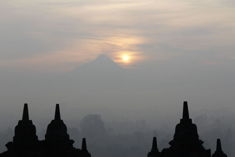 Silhouette Borobudur Temple with the mysteries forest surrounding during sunrise, Yogyakarta, Indonesia Ancient Borobudur Temple Java Yogyakarta Ancient Ancient Civilization Architecture Buddhism Built Structure Dawn Fog Forest History Mount Merapi Nature No People Outdoors Place Of Worship Religion Religious Architecture Sky Spirituality Sunrise Sunset