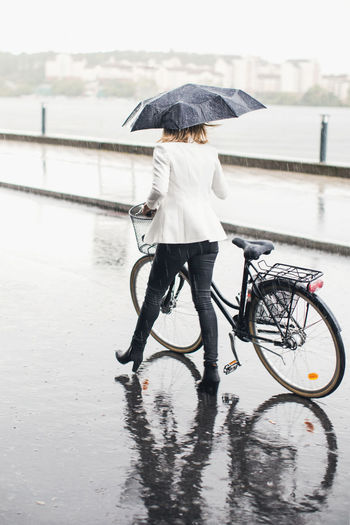 Rear view of person with bicycle on wet rainy day