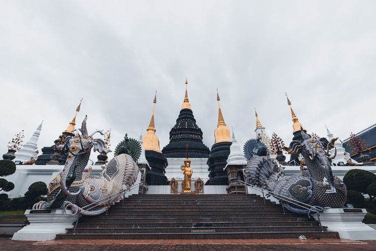 Low angle view of temple against cloudy sky