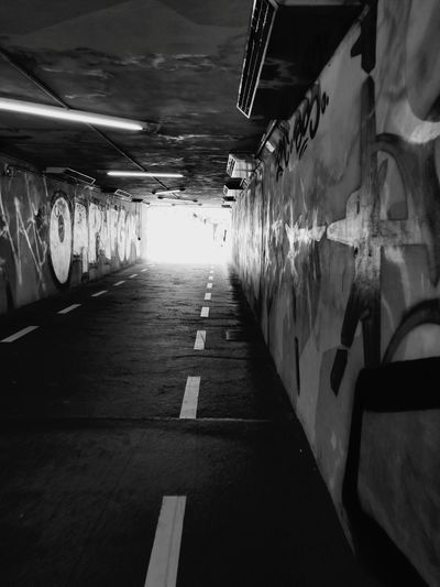 Underpass to Spielberk Center. Ways Of Seeing Czech It Out Black & White Photography Streetphotography Street Art Graffiti Writing Words Letters Painted Bike Path Walkway Perspective Perspective Photography Graffiti Art Wall - Building Feature People Walking Black & White City City Life Europe Reflection Tunnel Light At The End Of The Tunnel Underpass Underground Ceiling Light  Underground Walkway The Street Photographer - 2018 EyeEm Awards