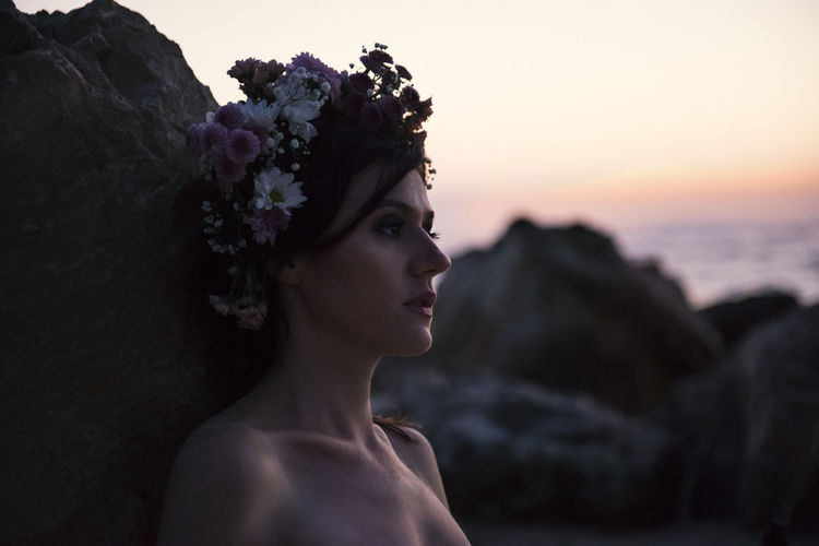 Woman wearing flowers while looking away against sky during sunset