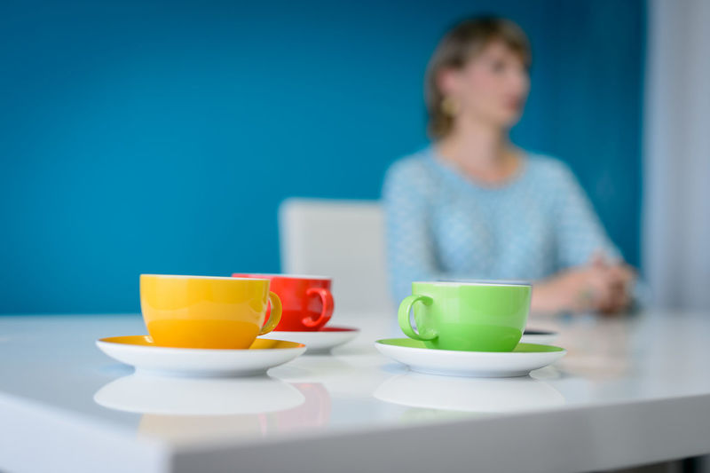 Colorful Cups On Table With Woman Sitting In Background