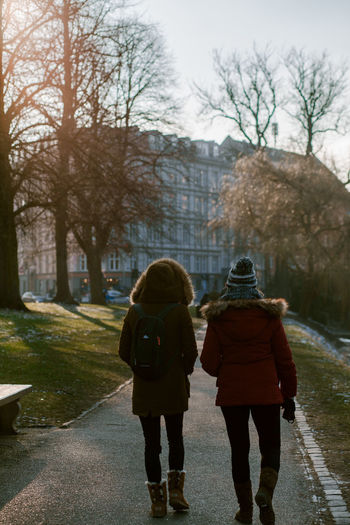 Rear view of women walking on footpath in winter