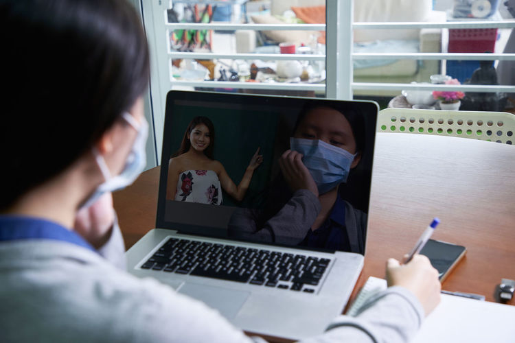 Rear view of girl wearing mask using laptop at home