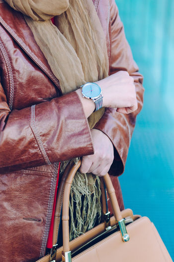 Elegant woman wearing silver wristwatch and brown leather coat holding leather brown handbag. Standing in front of blue background Elegant Elégance Fashion Leather Woman Wristwatch Adult Attitude Bag Clock Clothing Coat Formal Handbag  Identity Lifestyles Looking One Person Outfit person Personal Style Time Watch Wearing