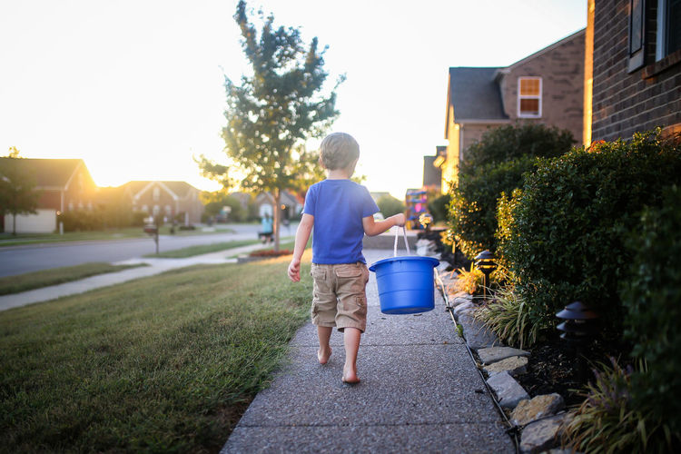 Rear view of boy carrying bucket while walking on footpath