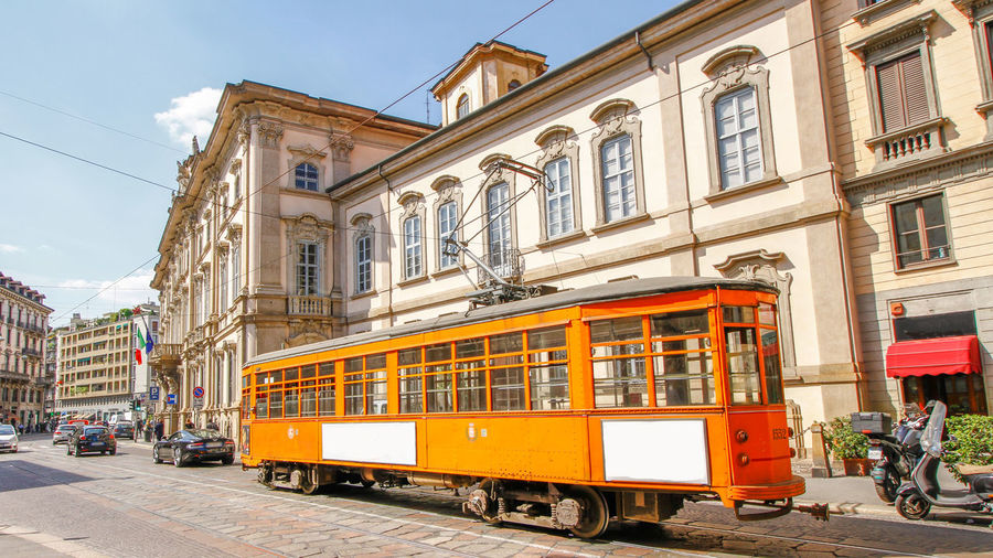 Architecture Building Building Exterior Built Structure Cable Car City Day Incidental People Land Vehicle Mode Of Transportation Outdoors Public Transportation Rail Transportation Railroad Track Real People Sky Street Track Train Train - Vehicle Transportation