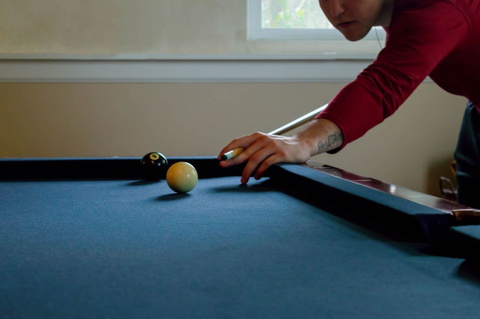 Young man lines up a shot while playing pool Recreation  Aiming Ball Billiards Hand Holding Human Hand Indoors  Leisure Activity Leisure Games One Person Playing Playing Pool Pool - Cue Sport Pool Ball Pool Cue Pool Table Real People Shooting Pool Skill  Snooker Sport Table Young Man