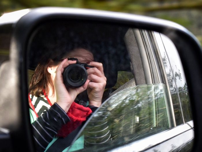 Reflection Of Woman On Side-View Mirror Photographing Through Camera While Sitting In Car