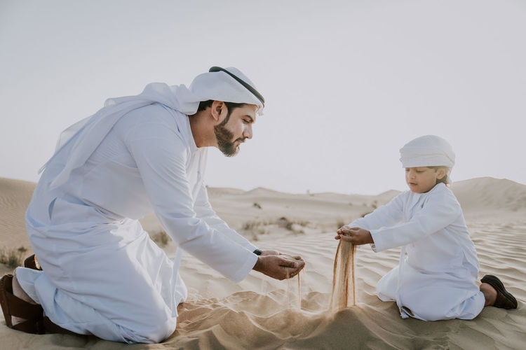 Father and son enjoying while crouching in desert