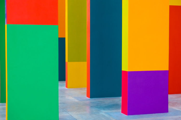 Abstract geometric pattern on concrete wall Architectural Column Architecture Blue Built Structure Choice Creativity Flooring Green Color In A Row Indoors  Multi Colored No People Orange Color Red Variation Vibrant Color Wall - Building Feature Yellow