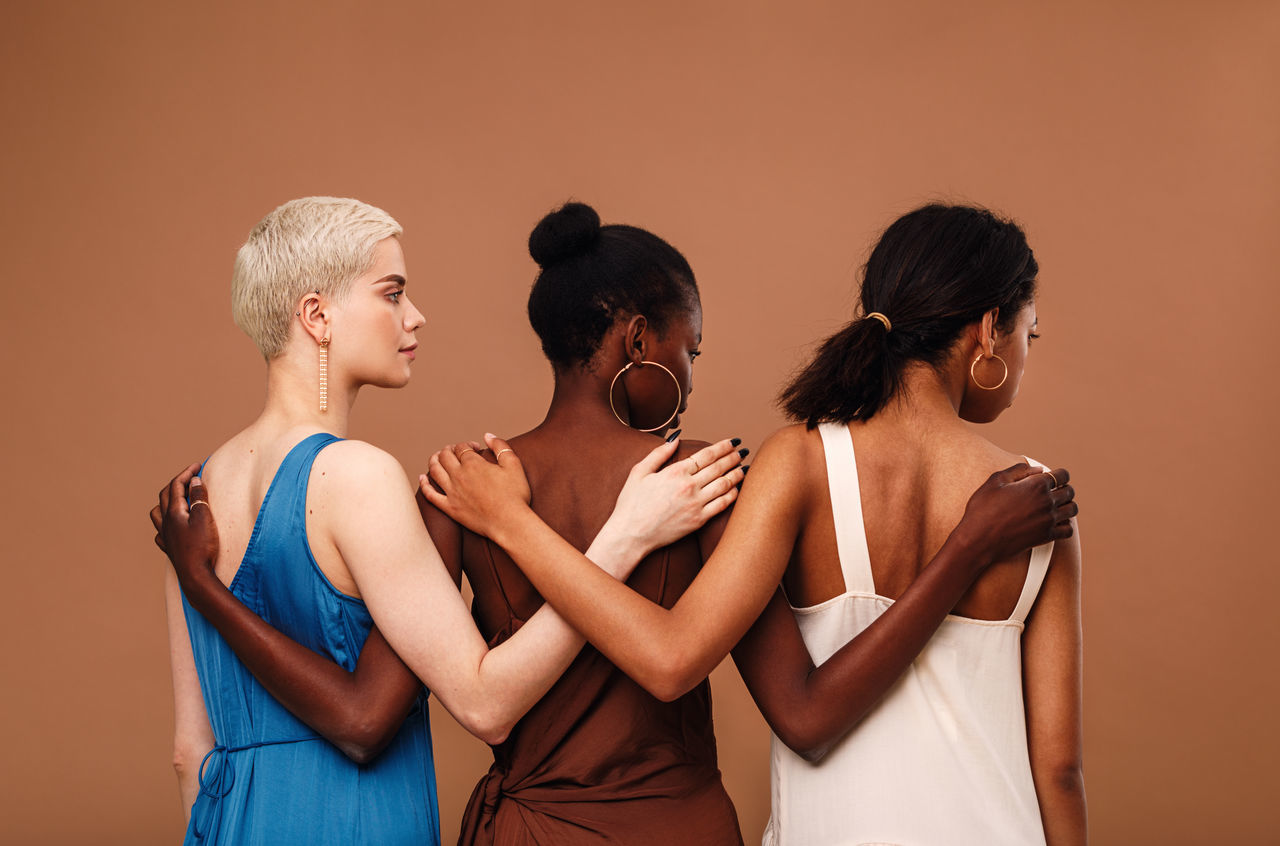 Multi-ethnic women with arm around standing against brown background