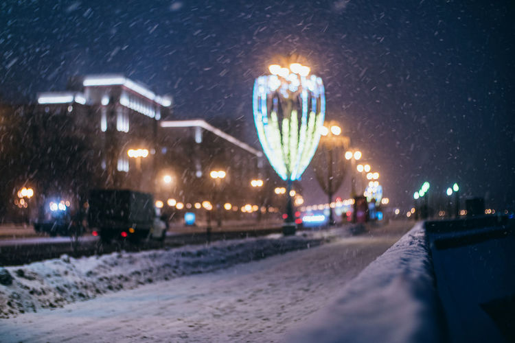 Illuminated city street during winter at night
