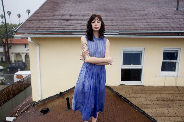 Portrait of young woman standing on wall