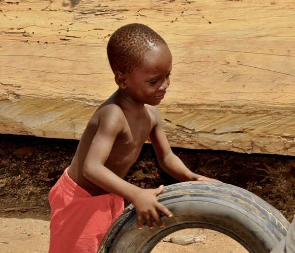 Shirtless Boy Playing With Tire While Standing Outdoors During Sunny Day
