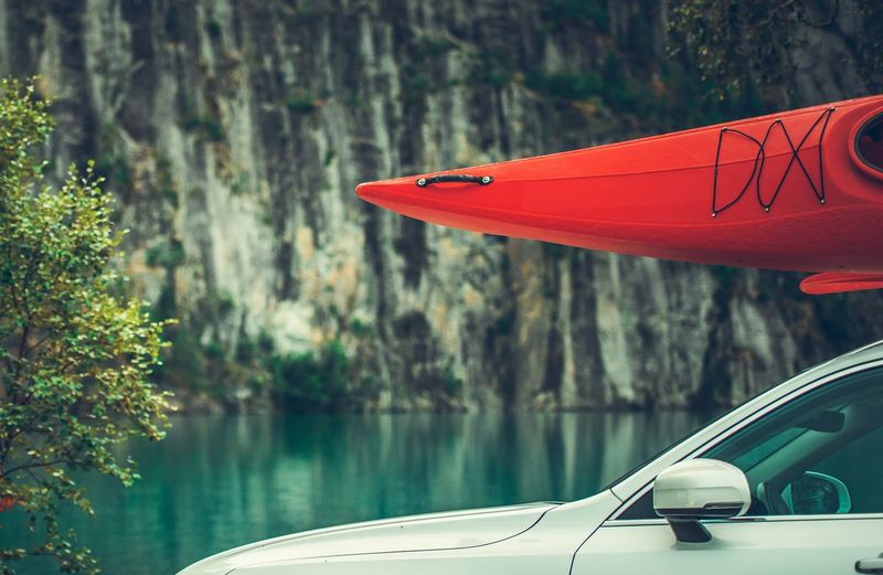 Summer Kayaking Tour. Red Kayak on the Car Roof. Water Sport Theme. Kayak Driving Tourism Kayaking Sport Roof Rack Vehicle Destination Vacation Mode Of Transportation Transportation Red Water Car Tree Focus On Foreground Motor Vehicle Nautical Vessel Day Plant Nature Lake No People Land Vehicle Reflection Travel Outdoors Beauty In Nature
