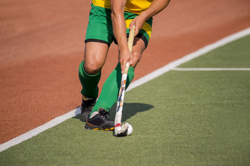 Field hockey player, in possesion of the ball, running over an astroturf pitch, looking for a team mate to pass to Field Hockey Fight Grass Action Active Athlete Ball Body Part Competition Competitive Sport Day Green Color Human Body Part Human Leg Human Limb Leisure Activity Lifestyles Low Section Men One Person Outdoors Playing Real People Shadow Shorts Skill  Sport Sunlight