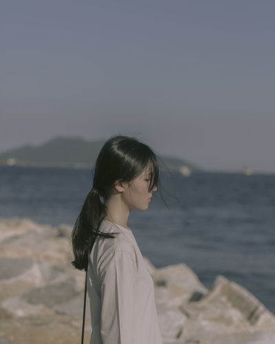 Side View Of Thoughtful Woman Standing At Beach Against Sky