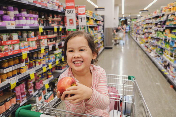 Happy little multiethnic girl sitting in a trolley, shopping cart at supermarket, grocery store Asian  Australia Family Happy Kids Trolley Cart Child Consumerism Customer  Food Girl Groceries Lifestyles Multicultural Retail  Shopping Shopping Cart Smiling Store Supermarket