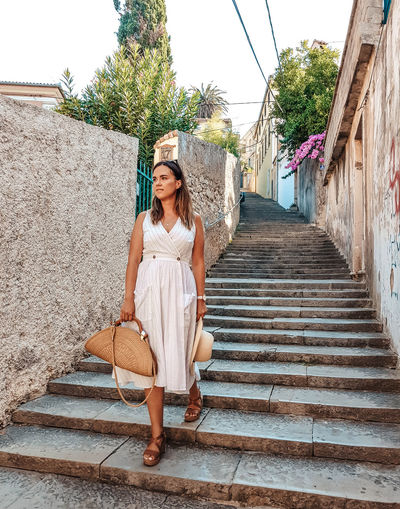 Young woman in white summer dress walking down the street of an old town.