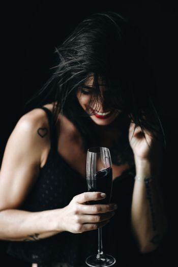 beautiful brunette girl millennial drinks red wine and have fun. One Person Indoors  Black Background Wine Drink Alcohol Refreshment Glass Front View Young Adult Portrait Wineglass Holding Young Women Food And Drink Studio Shot Adult Lifestyles Long Hair Headshot Hairstyle Drinking Beautiful Woman Dark Red Wine