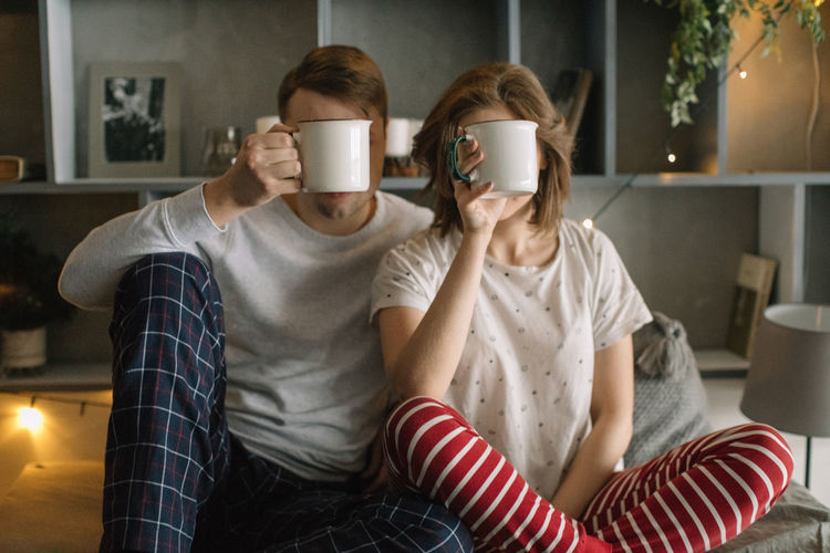 Fun Love Adult Bedroom Bonding Casual Clothing Couple - Relationship Front View Furniture Hairstyle Home Interior Indoors  Leisure Activity Lifestyles People Real People Sitting Sofa Three Quarter Length Togetherness Two People Women Young Adult Young Women