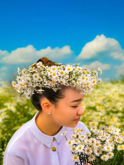 Young woman with yellow flowers on field against sky