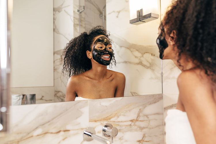Real People Lifestyles Indoors  Young Adult Curly Hair Black Face Mask Applying Standing Bathroom Mirror Reflection Smiling Happy Towel Spa Treatment Looking Young Females Hygiene Facial