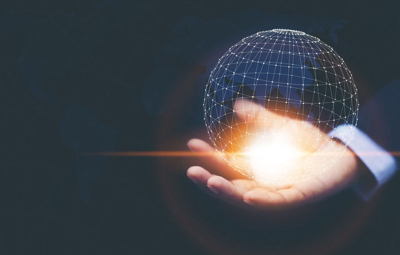 Digital composite image of business person holding illuminated globe