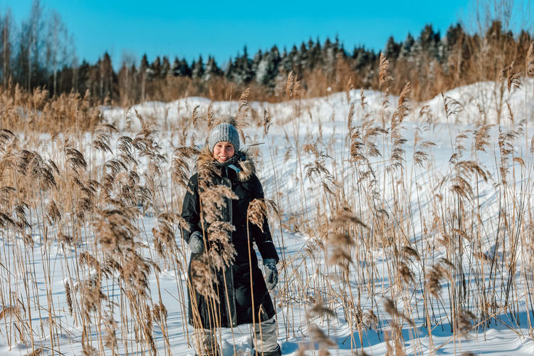 Woman standing on snow covered field