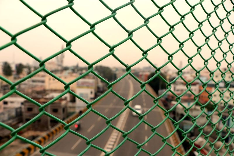 Full frame shot of chainlink fence against townscape