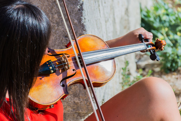 Close-Up Of Woman Playing Violin While Sitting Outdoors