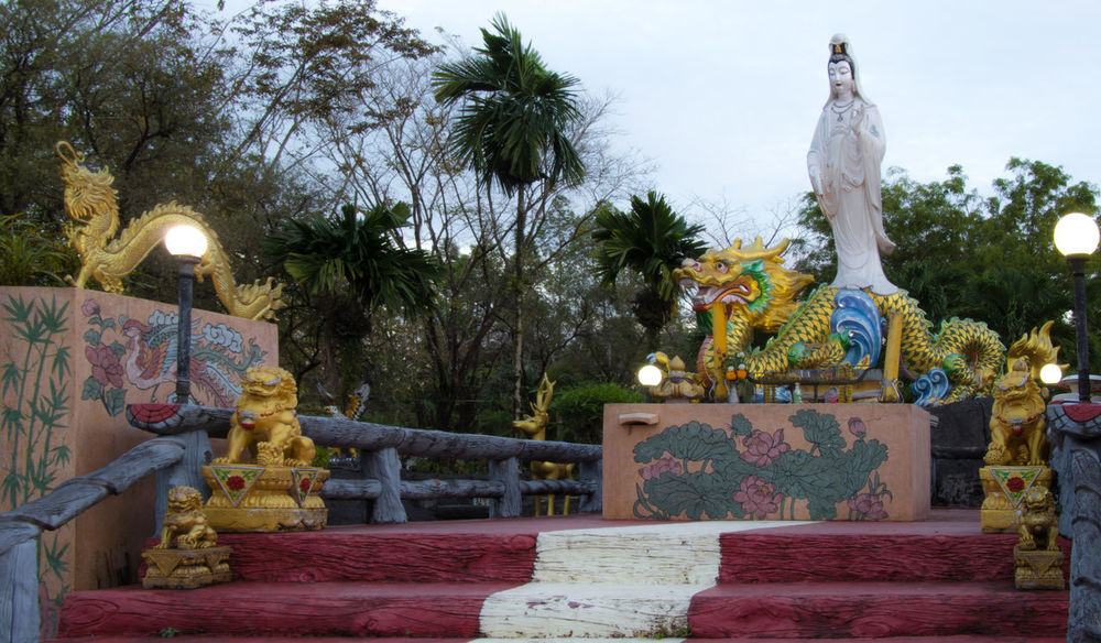 Gloden Statue of Guan Yin (or Kuan Im) , the Goddess of Mercy in Taoism with sun rise in Ranong , Thailand ASIA Architecture Asian  Buddha Buddhism Culture Buddhist God Tree Attraction China Day Guanyin Habour Landmark Low Angle View Mercy  No People Outdoors Religion Sky Symbol Yin