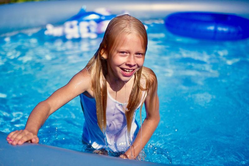Little blond long hair girl in blowed swimmingpool coming out of water Swimming Pool Happiness Smiling Leisure Activity Enjoyment Front View Lifestyles Day Blue Girl Little Girl Blowed Swimmingpool Live For The Story Live For The Story
