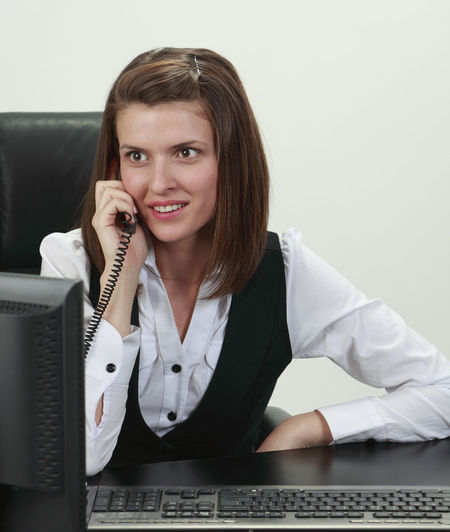 Portrait of a young woman on a phone against a white background. Front View One Person Portrait Young Adult Looking At Camera Smiling Phone Telephone Communication Young Woman Young Woman Smiling Businesswoman Woman Using Phone Woman On The Phone Call Phone Call Isolated Technology Office Computer Occupation Business Desktop Pc Business Person Landline Phone