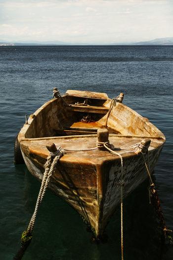 Boat moored in sea against sky