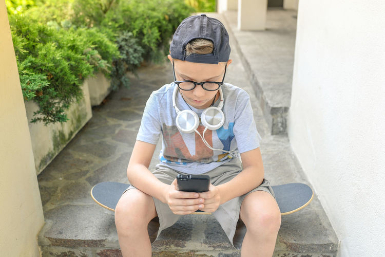 Boy Using Mobile Phone While Sitting On Steps