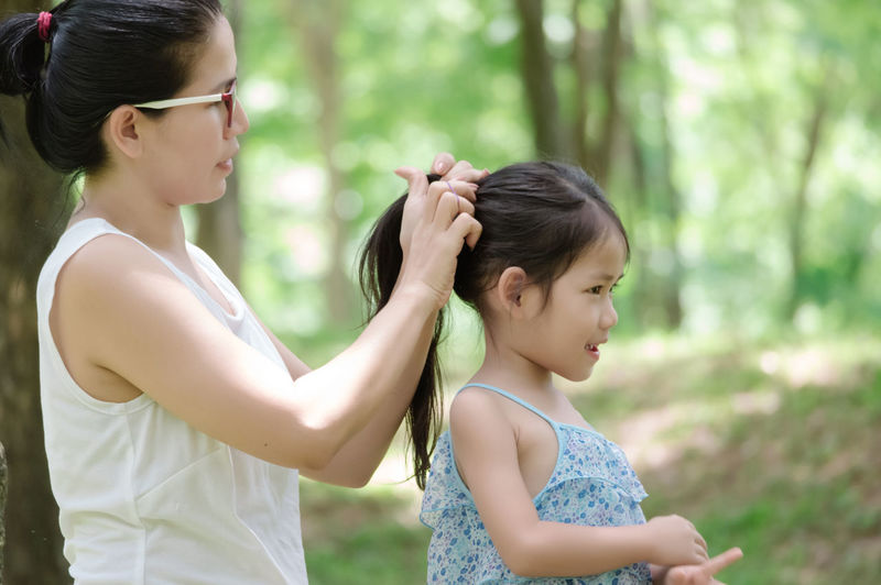 Side view of mother tying hair of daughter while standing in forest