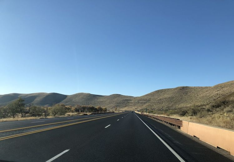 Desert highway in New Mexico. Clear Blue Sky Hillside Road Trip Empty Road Absence Highway Country Road Ranch Summer Sunlight The Way Forward Clear Sky Direction Copy Space Mountain No People vanishing point Diminishing Perspective Outdoors Dividing Line Blue Mountain Range Road Fieldscape New Mexico