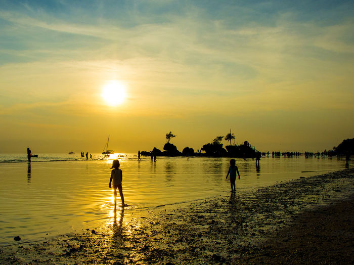 Silhouette children standing on shore at beach against sky during sunset
