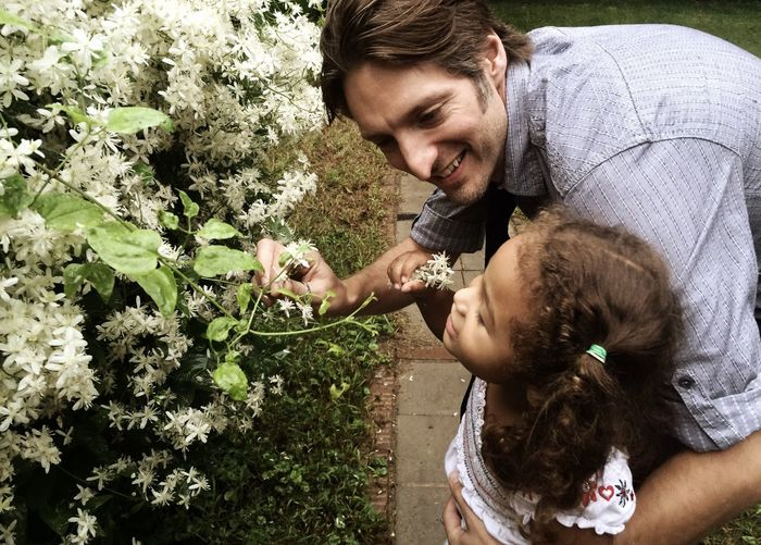 High angle view of father and daughter by flowering plants