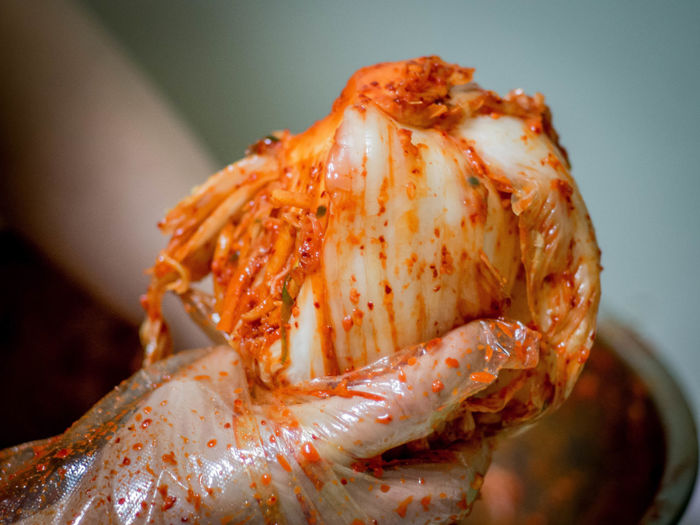 Cropped Image Of Hands Holding Kimchi
