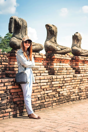 Full length of woman standing against statues on brick wall