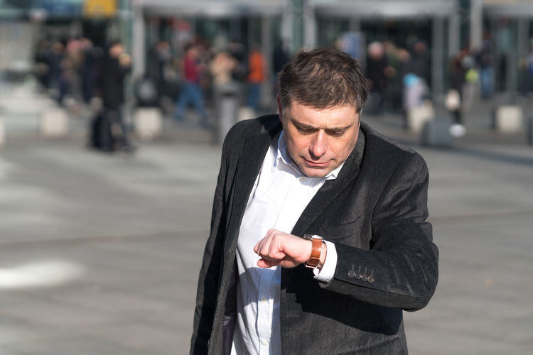 Man Checking Time On Wristwatch While Standing In City