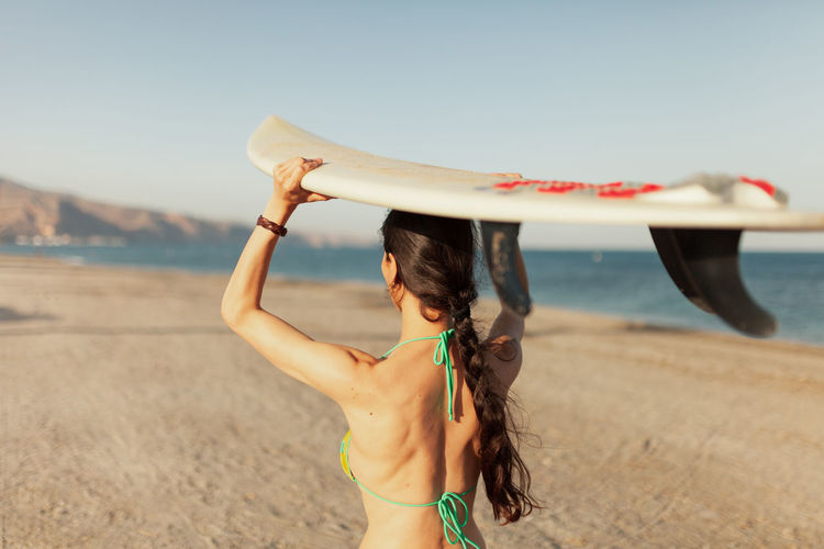 Rear view of woman carrying surfboard while walking at beach